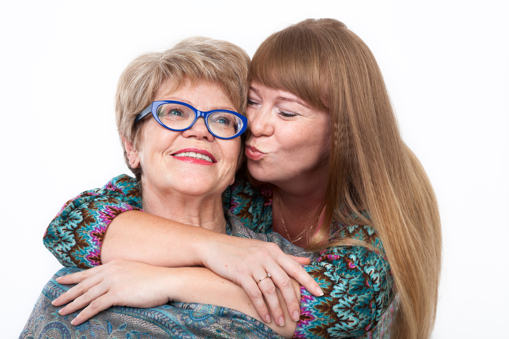 Adult daughter hugging and kissing elderly mother on cheek